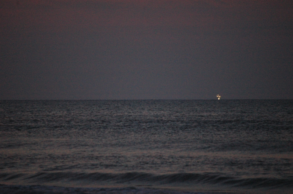 Oil rig lit up before sunrise in the Gulf of Mexico from Jamaica Beach, Galveston, TX