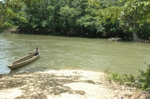 Canoe crossing a river between Kekchi villages, Peten, Guatemala